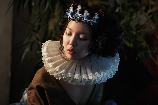 나뭇잎과 녹음이 우거진 소녀 공주 여왕의 예술 초상화, 마법의 드레스를 입은 아시아 여성의 멋진 낭만적인 이미지. 관능적인 부드러운 시선. 궁전의 소녀는 왕자를 기다리고 있습니다