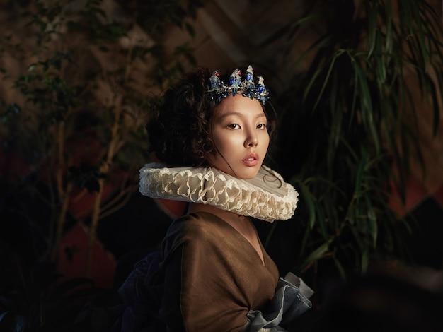 Художественный портрет женщины принцессы королевы в листве и зелени, сказочный романтический образ азиатской женщины в волшебном платье. чувственный нежный взгляд. женщина во дворце ждет принца