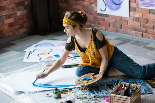 アートリラクゼーション。床に座って、抽象的なアートワークの絵画を楽しんでいる若い女性。