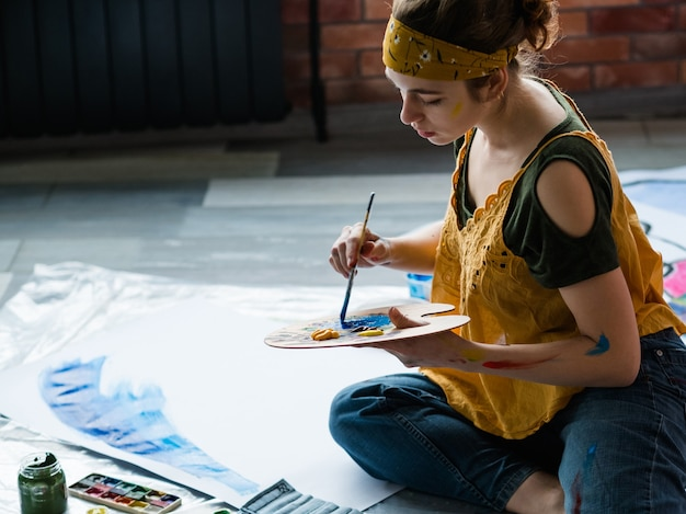 アートリラクゼーション。床に座って、アクリル絵の具パレットを使用して、抽象的なアートワークを作成する若い女性。