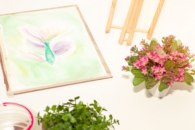 Art room in relax time and small pink flower plant pot. fish painting in living room.