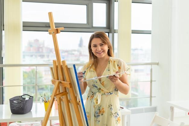 예술 학교, 창의성 및 여가 개념 - 스튜디오에서 이젤, 팔레트 및 페인트 브러시 그림을 가진 학생 소녀 또는 젊은 여성 예술가.