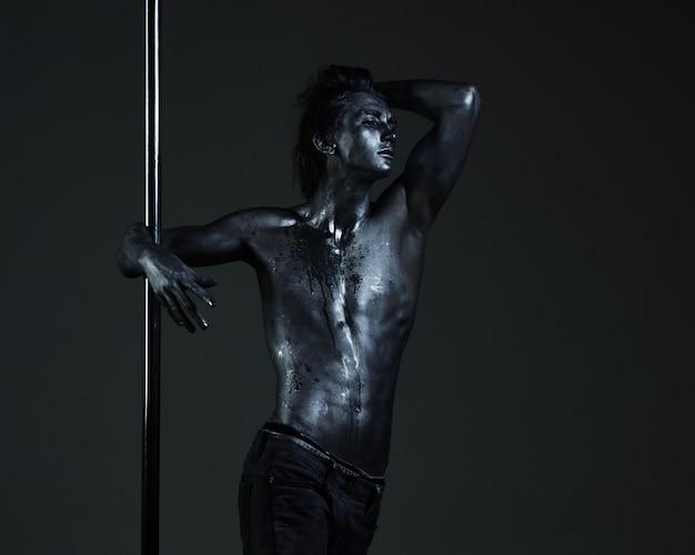 예술 섹시한 남자 몸 매력적인 섹시한 남자 극 춤 동작을 수행 쇼 트릭 남자가 극에 그림을 만든다