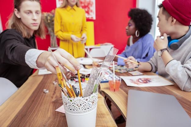アート学生。黒と白のシャツを着て鉛筆を取っているブロンドの髪の芸術学生のクローズアップ