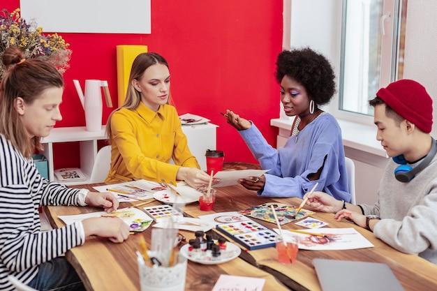 アートの学生。テイクアウトのコーヒーを飲み、週末に一緒に絵を描く4人の芸術学生