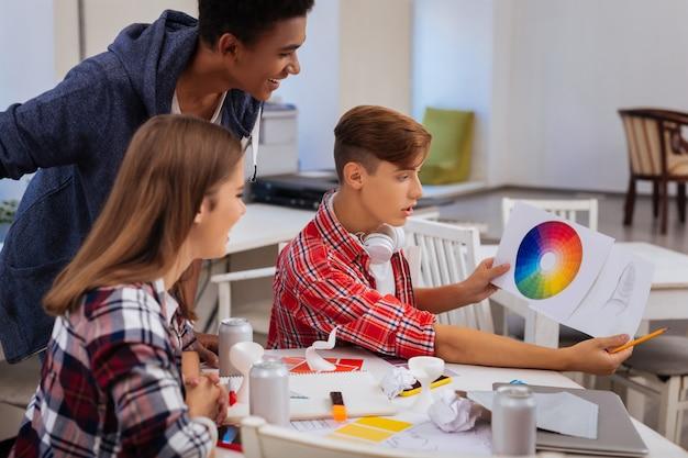미술 학생. 색상 팔레트를 보면서 호기심을 느끼는 유망한 창의적 미술 학생