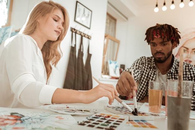 Студенты-художники. два талантливых перспективных студента-искусствоведа используют акварели во время работы над университетским проектом