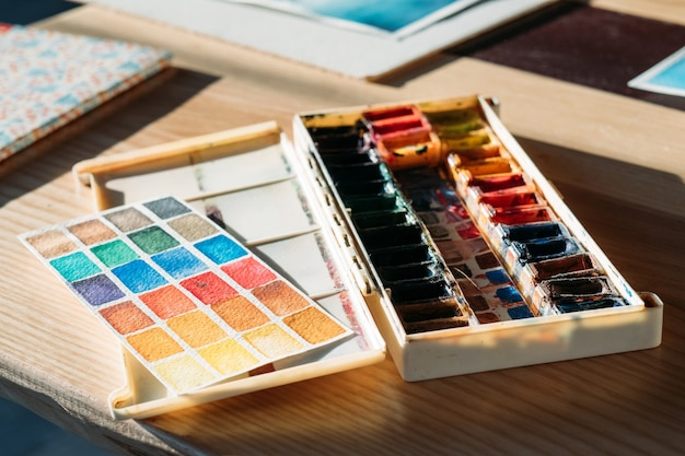 Art supplies at workplace. artist tools. watercolor paint set and color chart on desk.