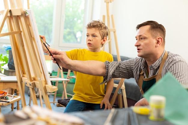 水彩画を扱う彼のかわいい生徒を助ける芸術の先生