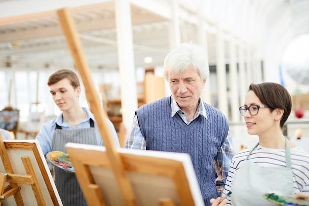 Учитель рисования помогает ученикам