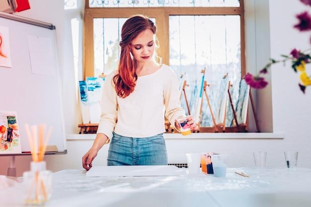 미술 선생님. 페인팅 스튜디오에 서있는 청바지와 베이지 색 셔츠를 입고 전문 재능있는 미술 교사