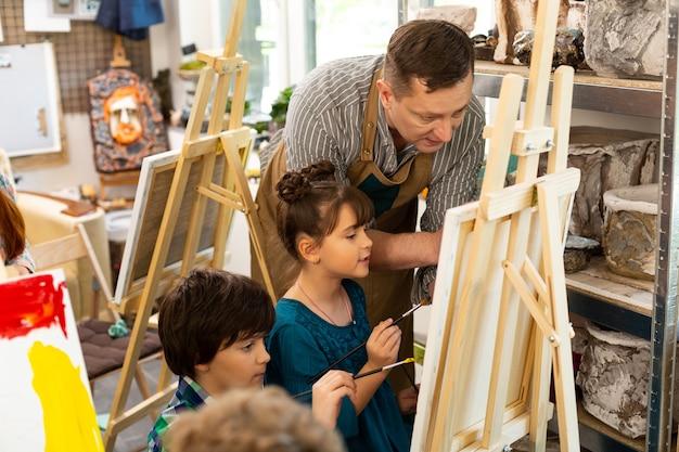 Учитель рисования разговаривает с мальчиком и девочкой, раскрашивая картинки