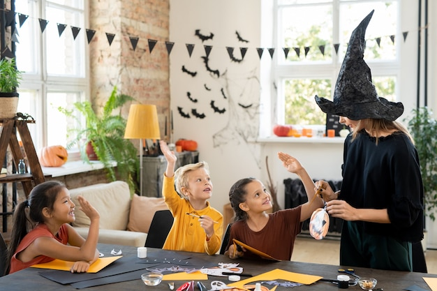 Art teacher in witches hat showing paper pumpkin craft to children and asking children about halloween traditions at class