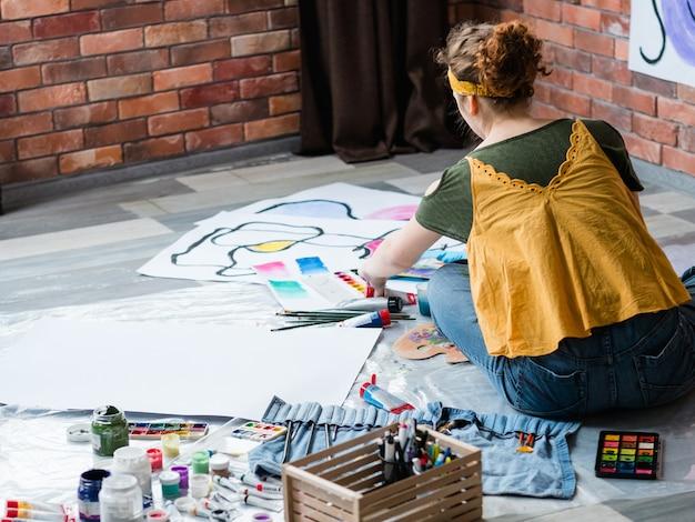 アートセラピー。水彩で抽象的なアートワークを描いて、床に座っている女性の背面図