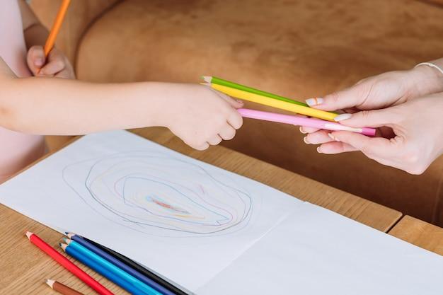 子供のためのアートセラピー。絵を描き始めるために鉛筆を取る少女の手。子供の芸術的なレジャーと創造的な絵画の趣味。