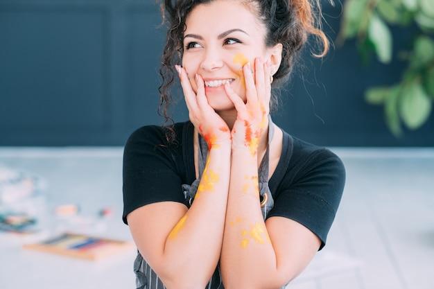 アートセラピー。幸せな女性は彼女の新しい趣味に興奮しました。カラフルなペンキで顔や手が汚れています。