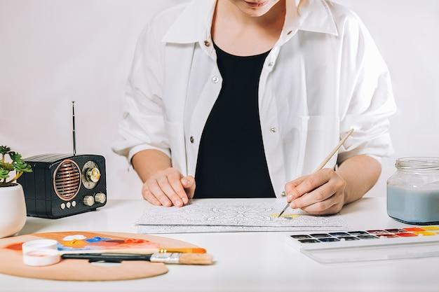 Арт-терапия или самовыражение для взрослых. молодая женщина раскраски антистрессовая книга, концепция выражения вдохновения психического благополучия и творчества.