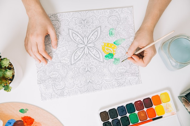 Арт-терапия или самовыражение для взрослых. молодая женщина раскраски антистрессовая книга, концепция психического благополучия. рабочее пространство художника - краски, карандаши, кисти, палитра.