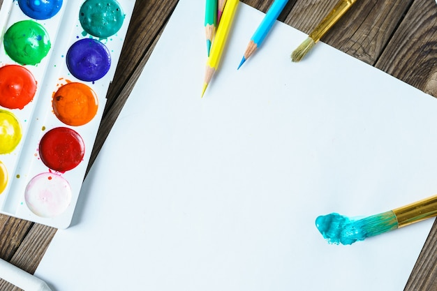 미술 도구. 나무 배경에 빈 흰색 종이가 있는 수채화 물감 및 브러시를 닫습니다.