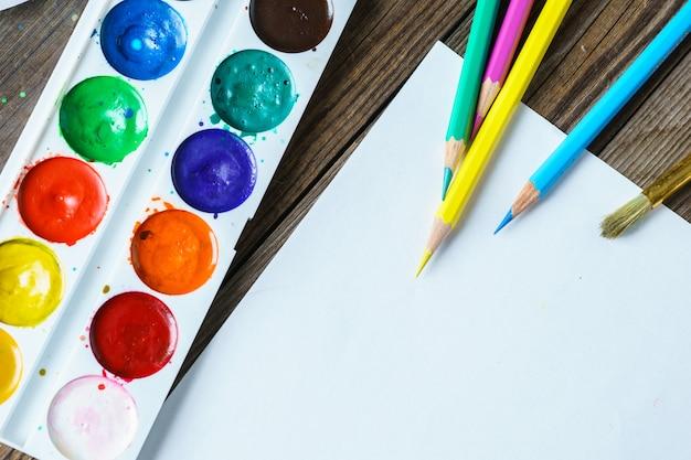 アートツール。水彩絵の具や木製の背景の空白の白い紙とブラシをクローズアップ。