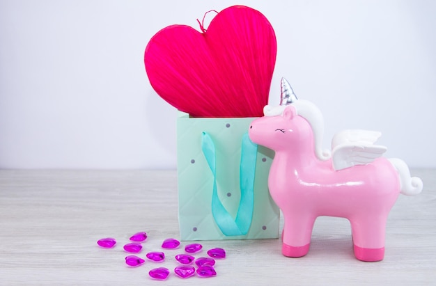 Art valentine's greeting card. red heart in a gift box. toy pink unicorn on a light background. valentine's day gift