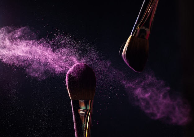 Art of visage. closeup photo of two professional black make-up brushes with purple powder isolated on black background with copy place.