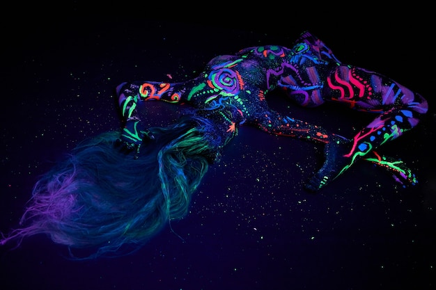 Art woman body art on the body dancing in ultraviolet light. bright abstract drawings on the girl body neon color