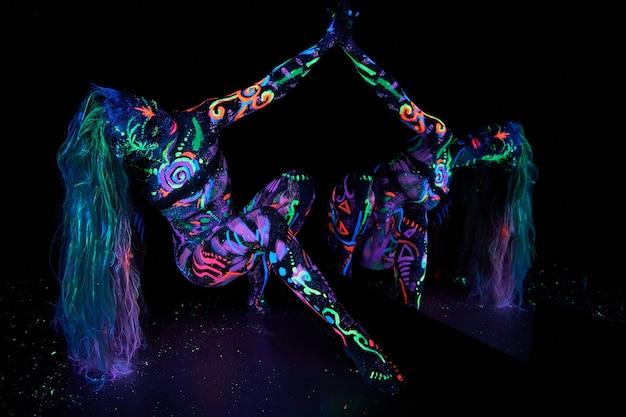 Art woman body art on the body dancing in ultraviolet light