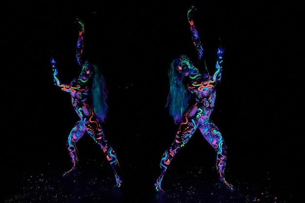 紫外線で踊る体のアート女性のボディーアート。女性の体のネオンカラーの明るい抽象画。色付きの髪と顔。ノイズ、焦点が合っていない