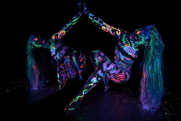 紫外線で踊る体のアート女性のボディーアート。女性の体のネオンカラーの明るい抽象画。色付きの髪と顔