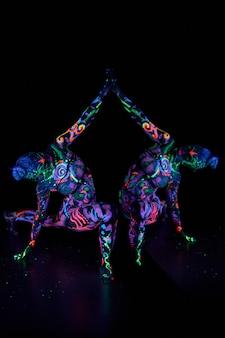 Художественный женский боди-арт на теле танцует в ультрафиолете