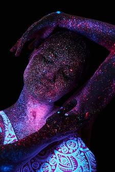 紫外線でアートウーマンコスモス。全身が色のついた水滴で覆われています。暗闇の中でポーズをとる少女。ノイズ、焦点が合っていない