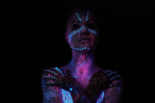 Art woman cosmos in ultraviolet light. entire body is covered with colored droplets
