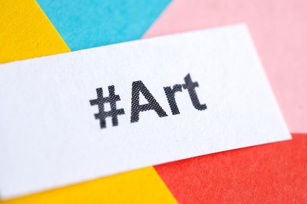 Популярный хэштег «art» напечатан на белом листе бумаги на разноцветной бумаге