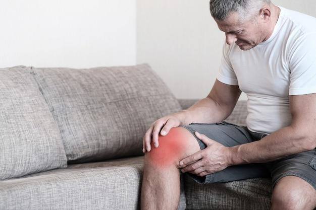 関節炎は関節の病気です。ソファに座って、ひざを耐え難いほどの痛みから圧迫している男性。