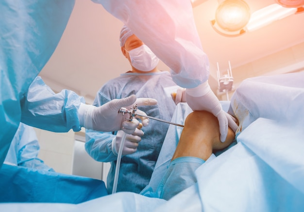 Arthroscope surgery. orthopedic surgeons in teamwork in the operating room with modern arthroscopic tools. knee surgery.