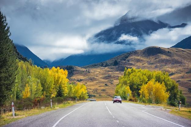 Arthursで道路を走っている車は、ニュージーランドで、秋にはカラフルな木々があります。