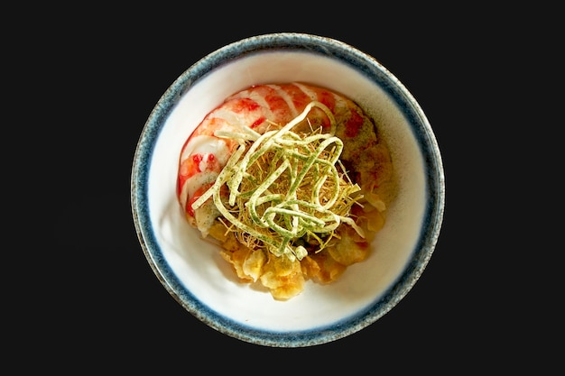 하얀 그릇에 게와 야채 칩을 곁들인 아티초크 샐러드. 검정색 배경에 고립. 레스토랑 음식