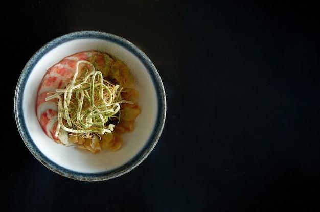 흰색 그릇에 게와 야채 칩을 곁들인 아티 초크 샐러드. 블랙 테이블에 격리. 레스토랑 음식