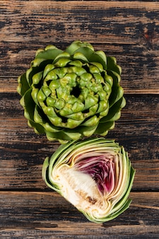 Artichoke and slice with top view on a dark wooden