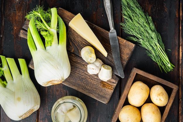 フェンネル、ジャガイモ、パルメザンチーズの材料を使ったアーティチョーク、古い木製のテーブル、フラットレイ