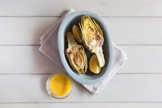 Artichokes and lemons on the plate. served with sauce. white wooden background. this product has one of the highest antioxidant capacities