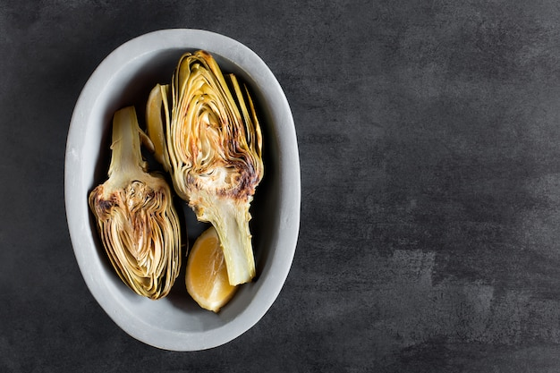 Artichokes and lemons on the plate. this product has one of the highest antioxidant capacities. chalkboard as background