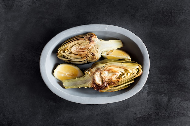 Artichokes and lemons on the plate. this product has one of the highest antioxidant capacities