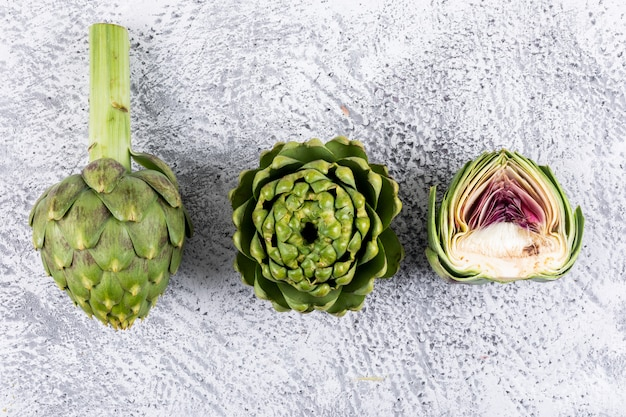 Artichokes and a slice on a light gray . top view.