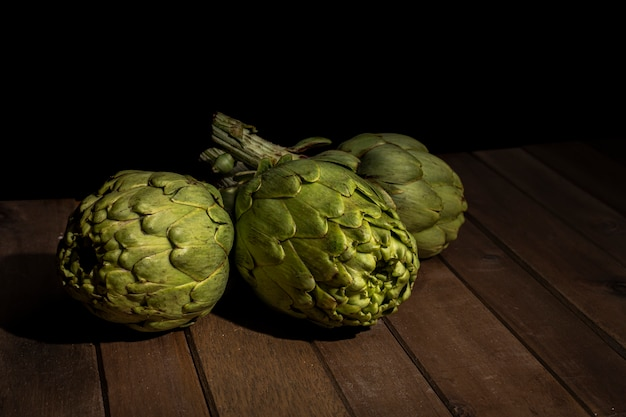 Artichokes on wooden table with black background.