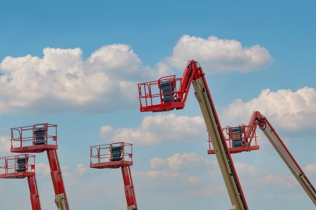 굴절식 붐 리프트. 공중 플랫폼 리프트. 푸른 하늘에 대 한 망원경 붐 리프트입니다. 임대 및 판매용 이동식 건설 크레인. 유지 보수 및 수리 유압 붐 리프트 서비스. 크레인 대리점.