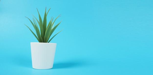 青い背景の上の人工サボテン植物またはプラスチックまたは偽の木。それは分離されています
