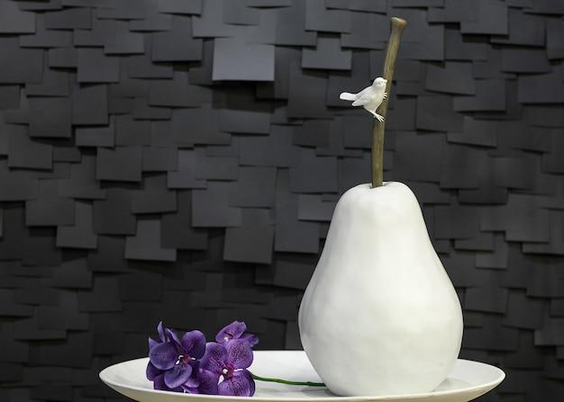 Искусственная керамическая груша на тарелке с птицей и цветком на черном фоне в виде плитки