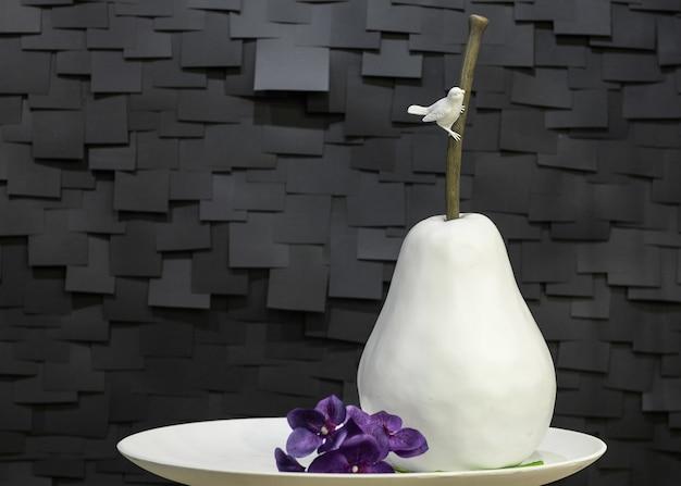 Искусственная керамическая груша на тарелке с птицей и цветком на черном фоне